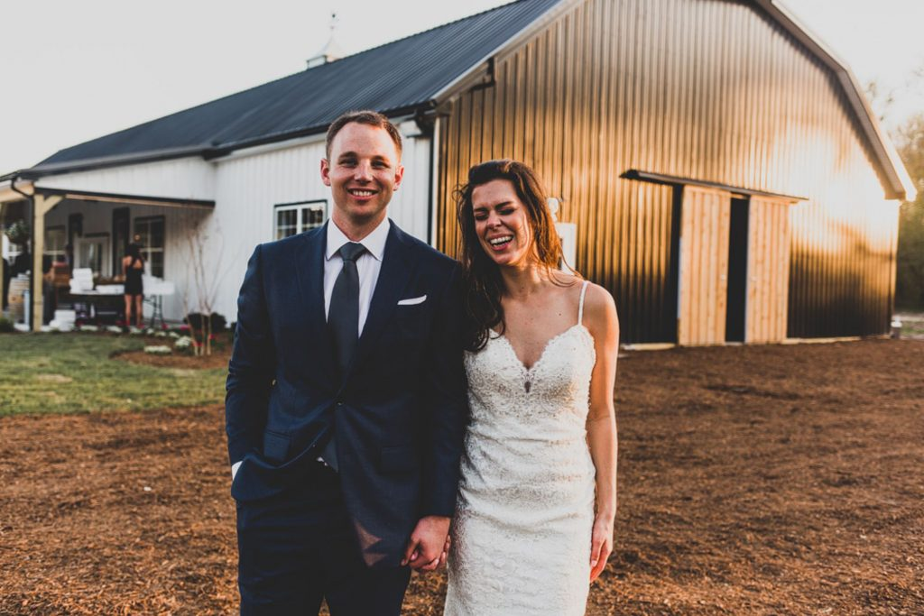 A wedding couple is holding hands and standing in front of the Smokey Hollow wedding venue in Delaware.