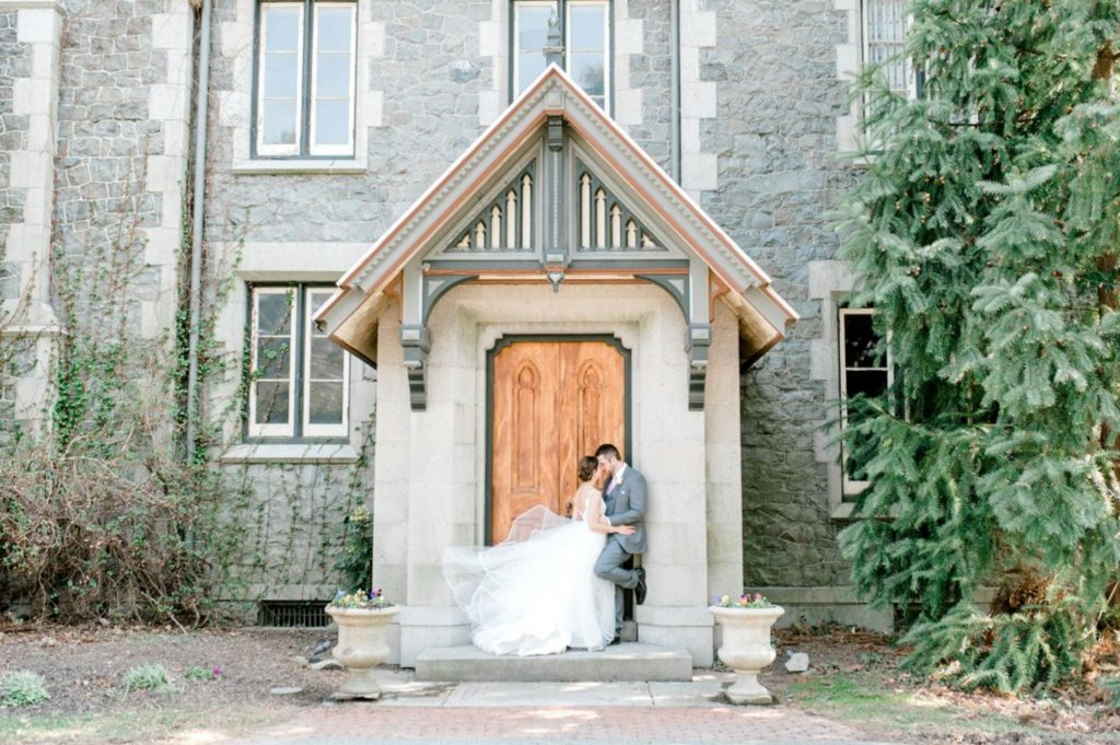 A wedding couple is holding each other and standing in front of the Carriage House at Rockwood Park in Delaware.