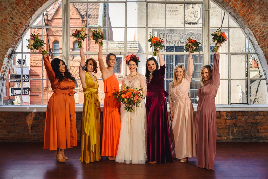 A bride and her bridesmaids are holding flower bouquets.