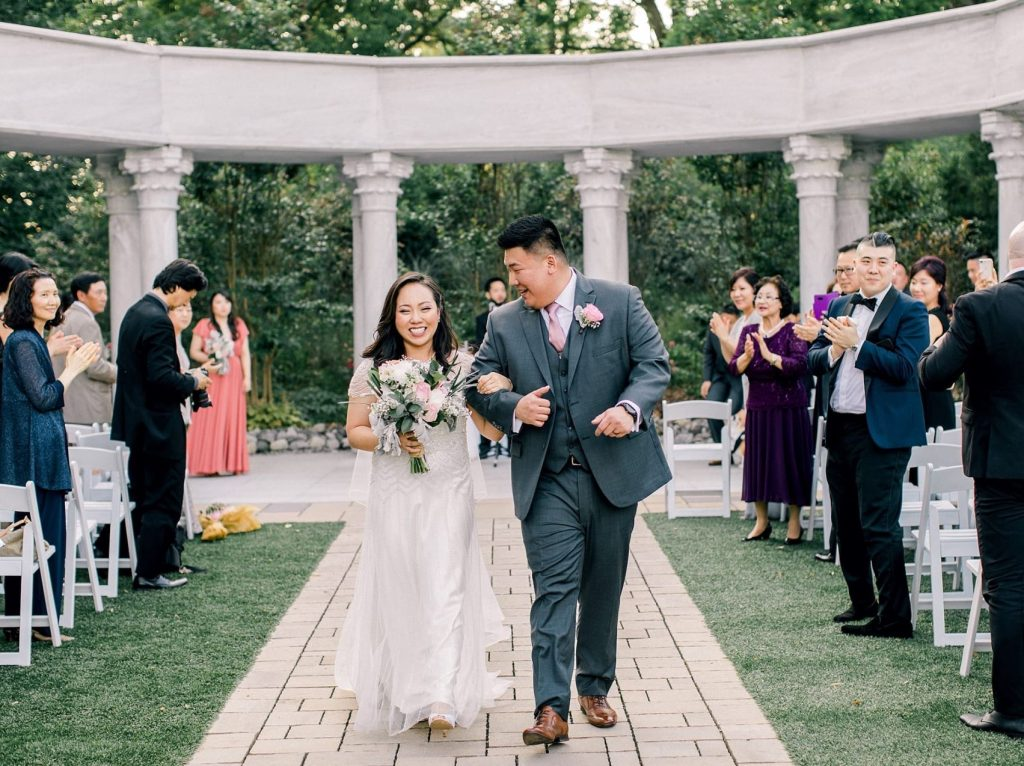 A wedding couple is walking back the aisle with their guests cheering at them.