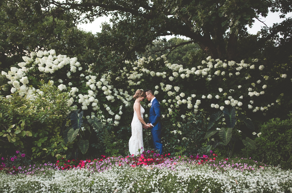 A wedding couple is holding hands and facing each other in the Boerner Botanical Gardens, one of the wedding venues Wisconsin.