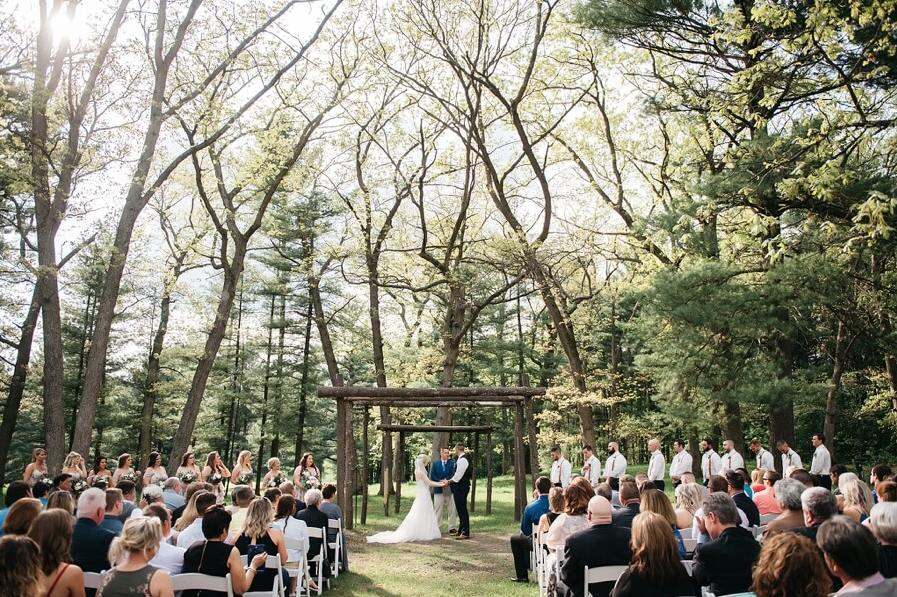 A wedding couple is standing at the altar in a forest with their guests sitting in front of them at the Chula Vista Resort in Wisconsin.
