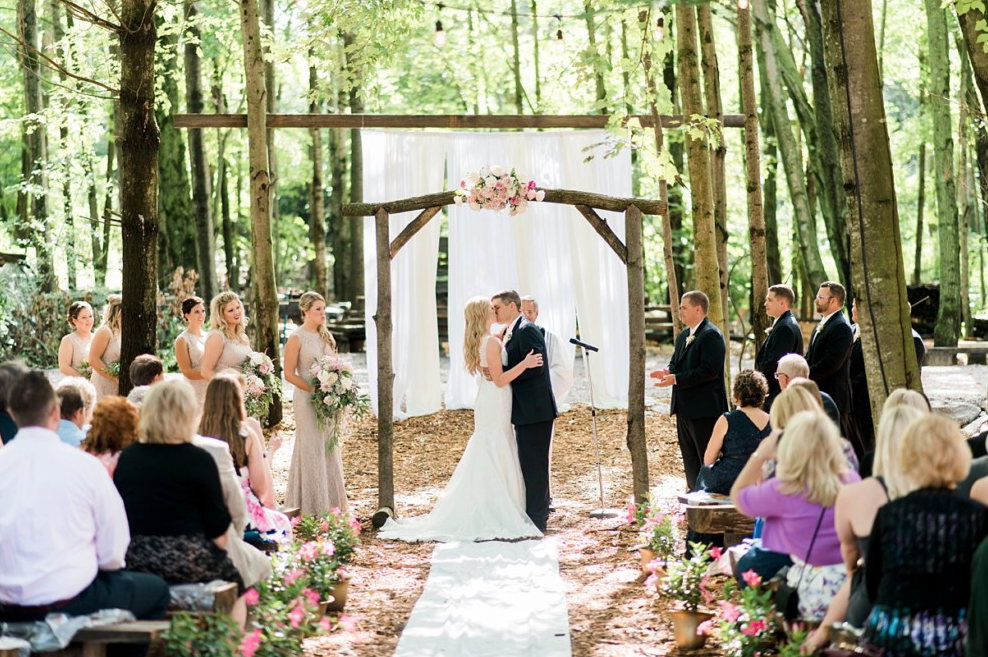 A wedding couple is kissing each other at the Swan Barn Door wedding venue in Wisconsin.