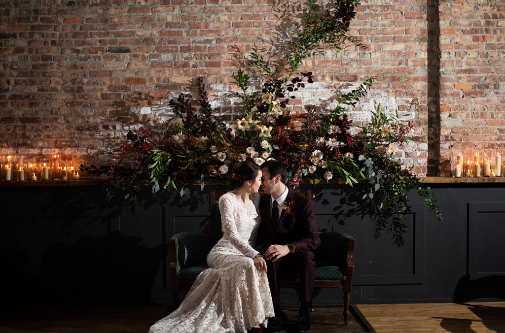 A wedding couple is sitting on a couch at the Mercantile Hall, one of the wedding venues Wisconsin.
