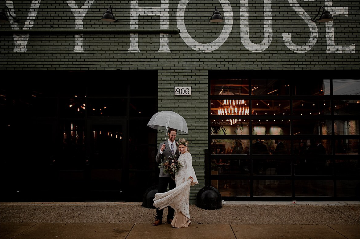 A wedding couple is standing in front of the Ivy House in Wisconsin.