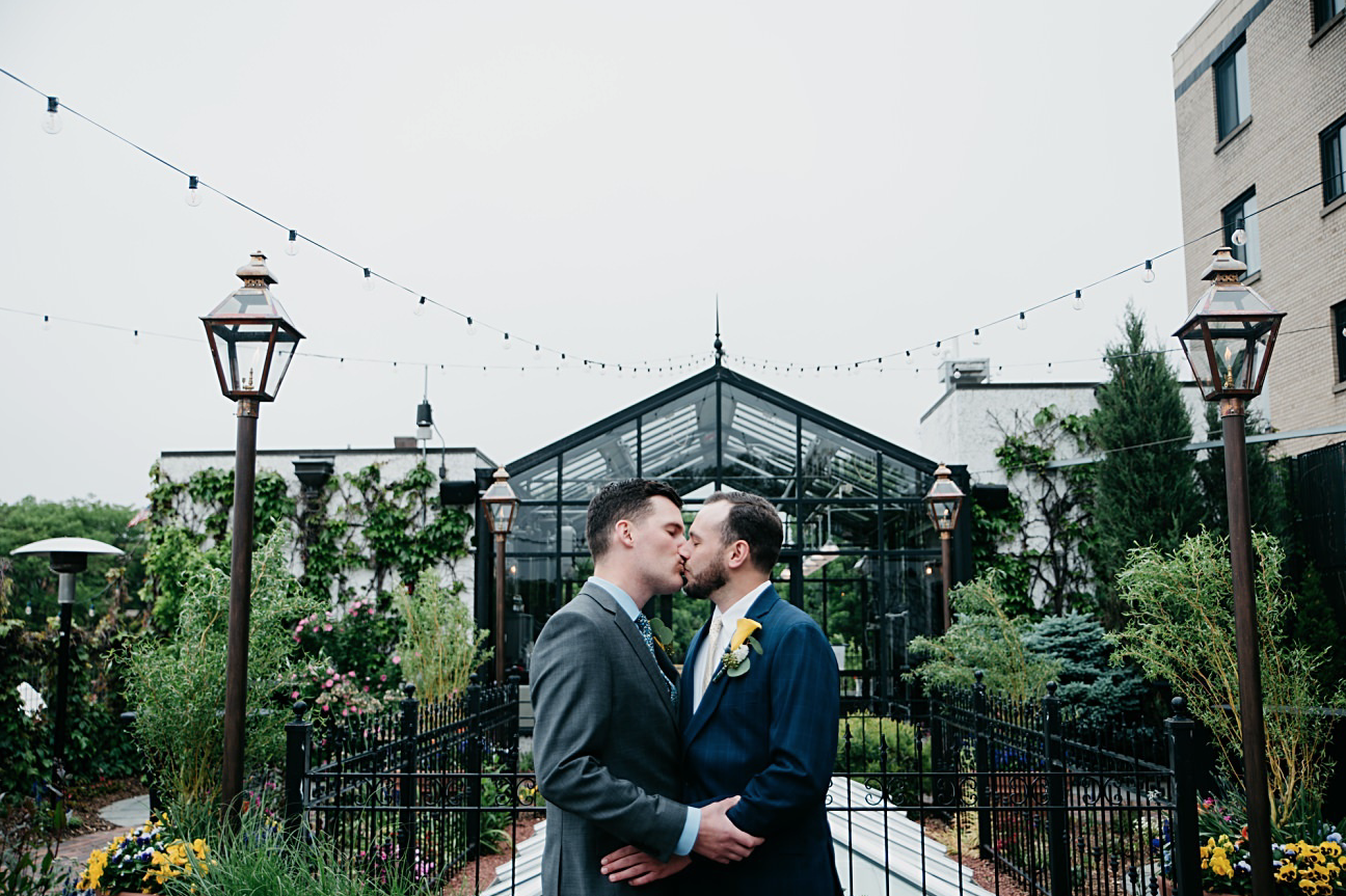 A wedding couple is kissing each other in front of a greenhouse at the Atrium, one of the wedding venues in Wisconsin.