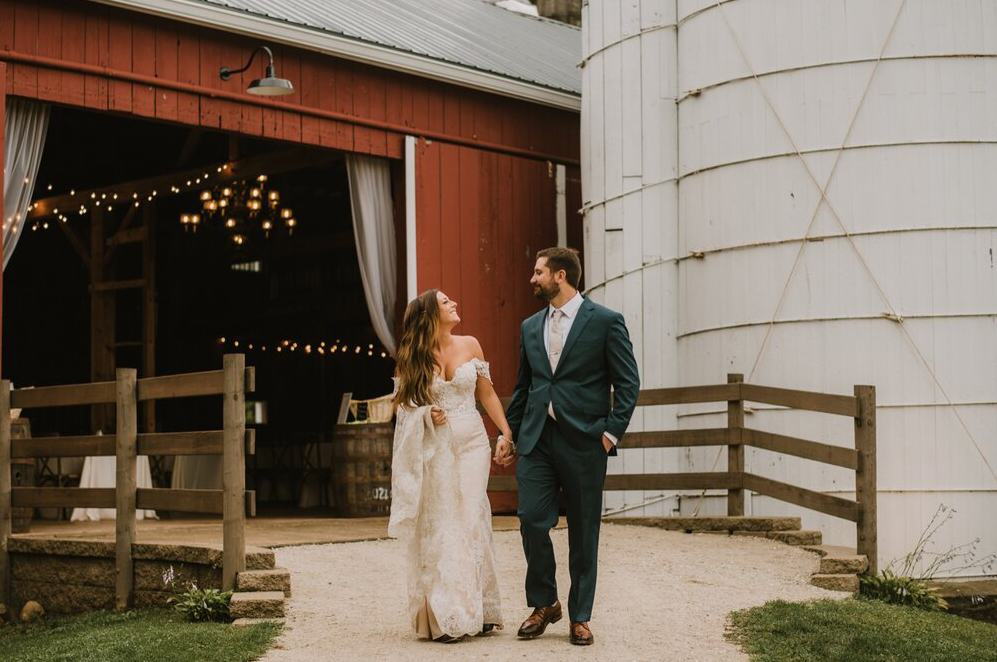 A wedding couple is holding hands and walking out of a barn in Wisconsin.