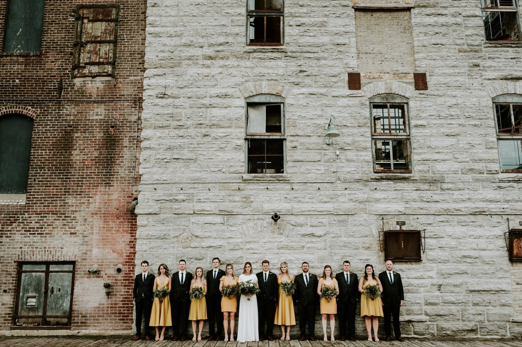 A wedding couple and their bridesmaids and groomsmen are standing in front of the Mill City Museum.