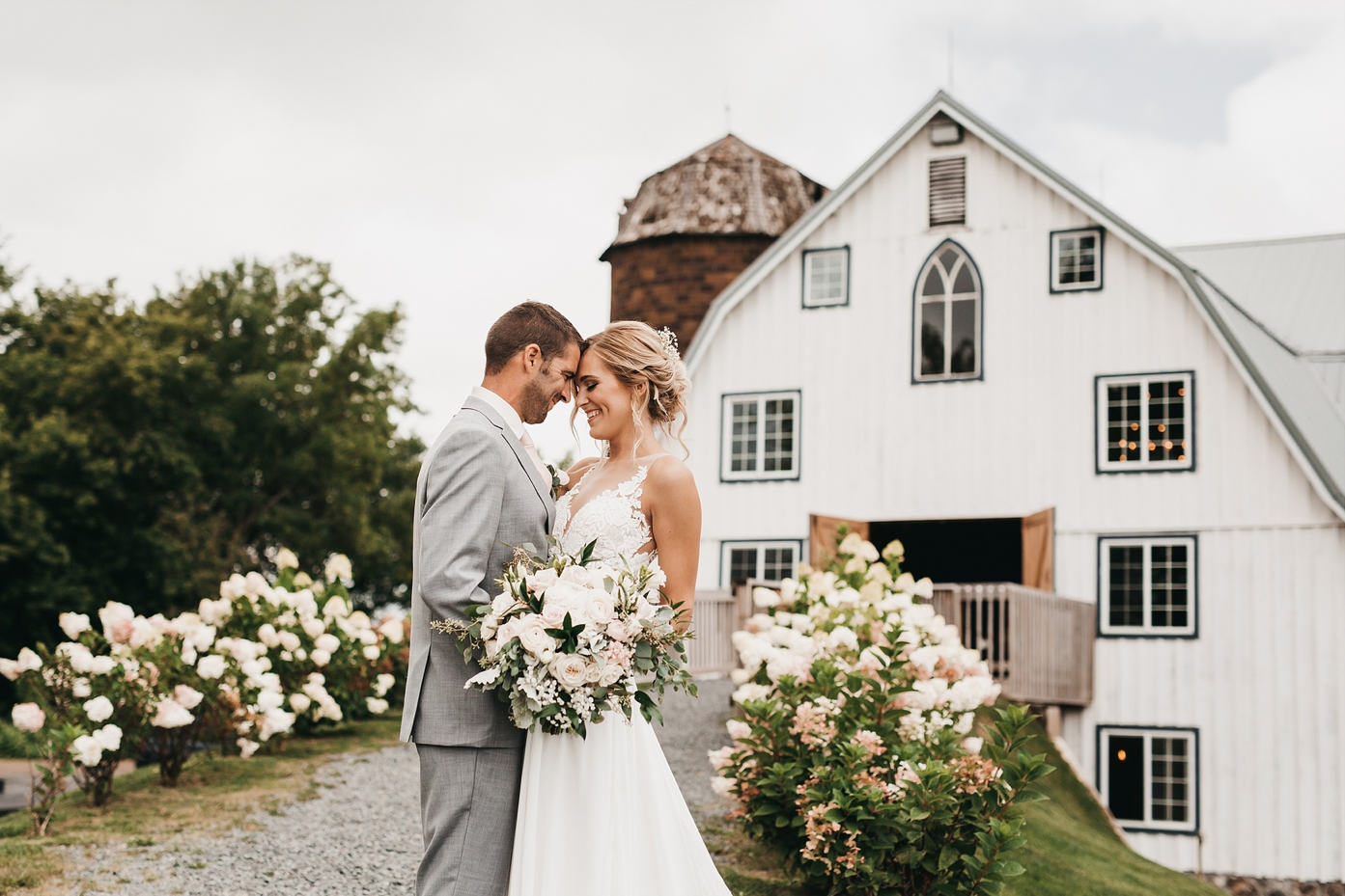 A wedding couple is holding each other at the Bloom Lake Farm.