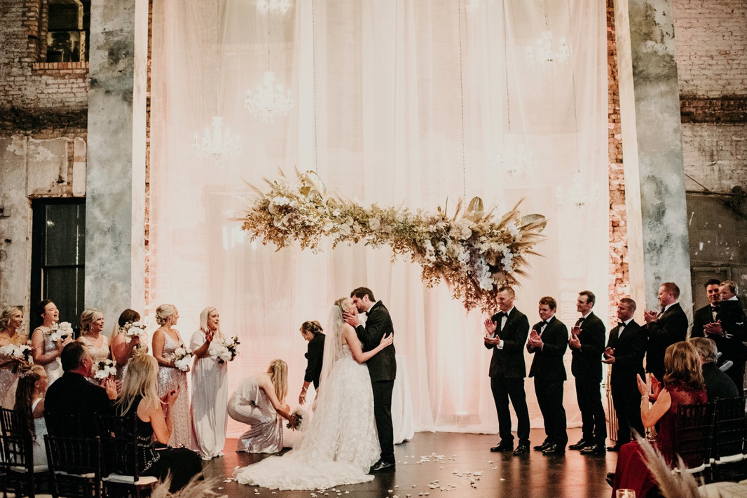 A wedding couple is kissing each other at the Aria wedding venue.