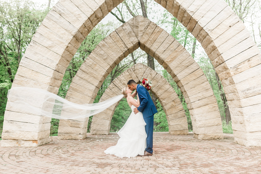 A wedding couple is kissing each other in front of stone arches at the Celebration Farm in Iowa.