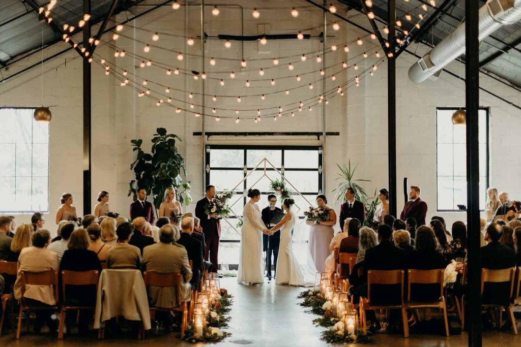 A wedding couple is standing at the altar at PAIKKA, one of the Minnesota wedding venues.