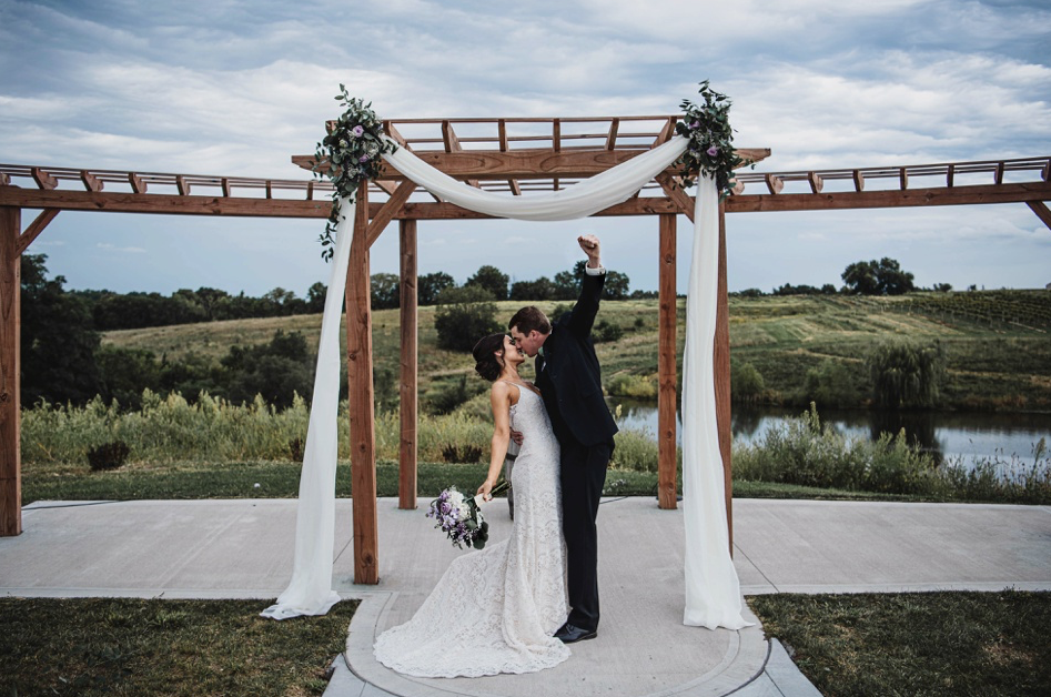 A wedding couple is kissing each other and standing at the Carper Vineyard and Winery.