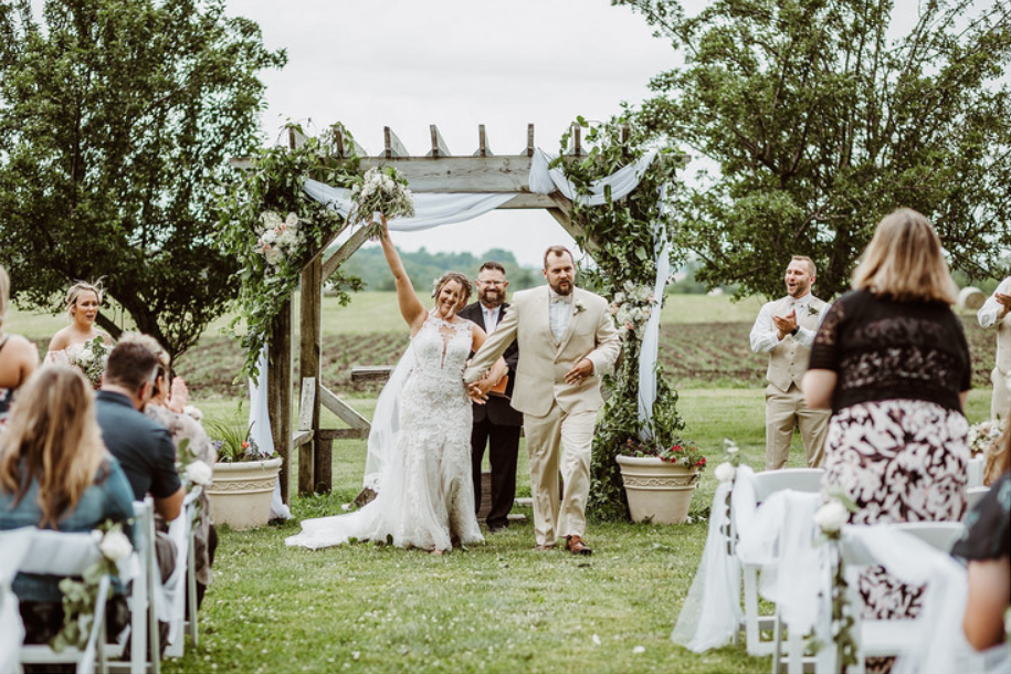 A wedding couple just got married and is smiling at their guests.