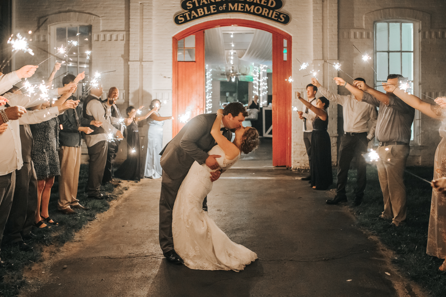A wedding couple is kissing each other and their guests are holding sparklers at one of the wedding venues in Kentucky.