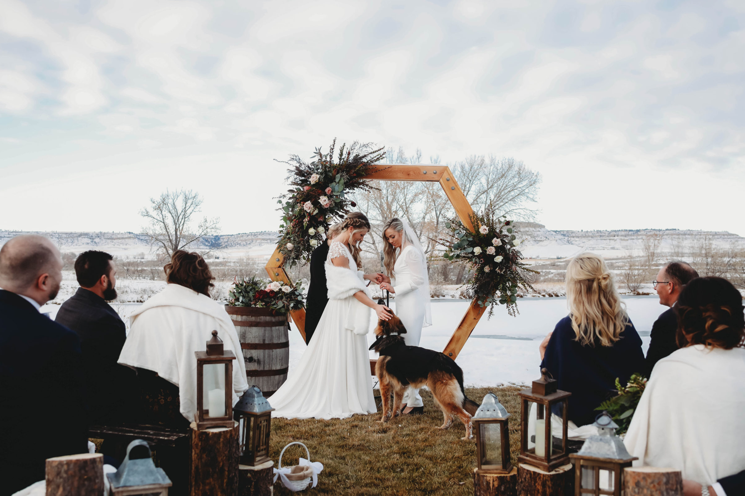 A wedding couple and their dog is standing at the altar at Camelot Ranch, one of the Montana wedding venues.