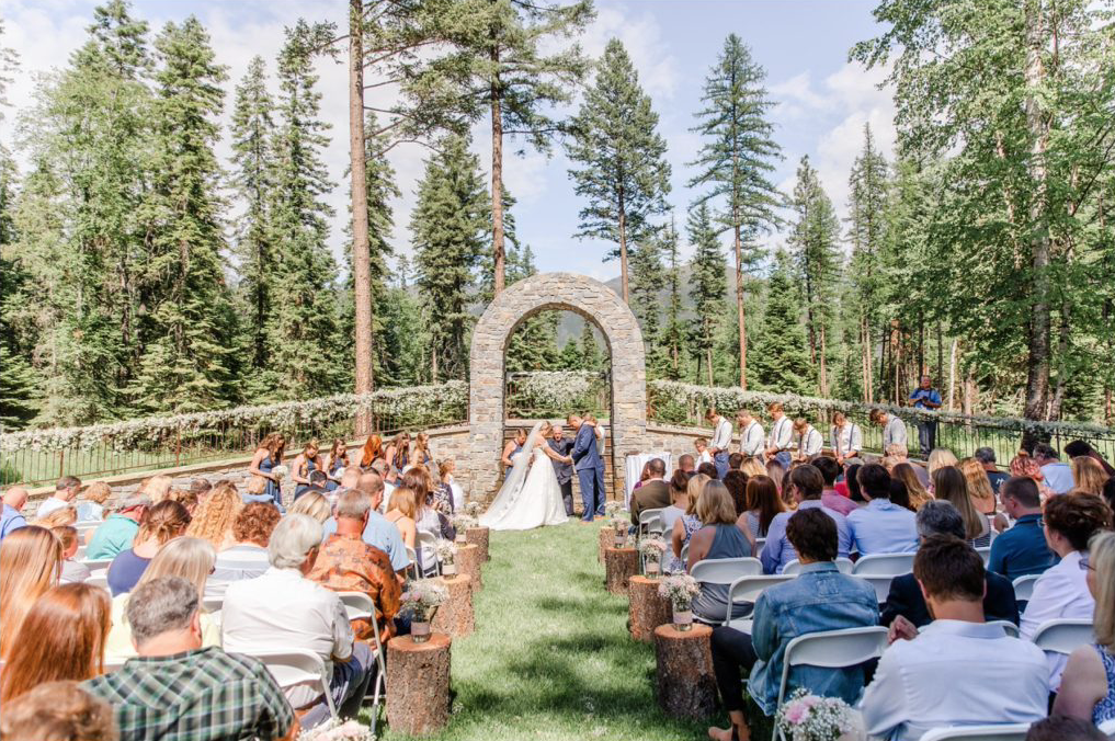 A wedding couple is standing in front of a stone arch and is getting married.