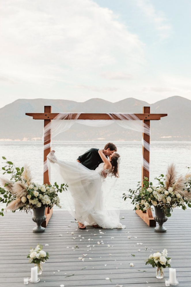 A groom is kissing his bride at the Flathead Lake Forevers in Montana.