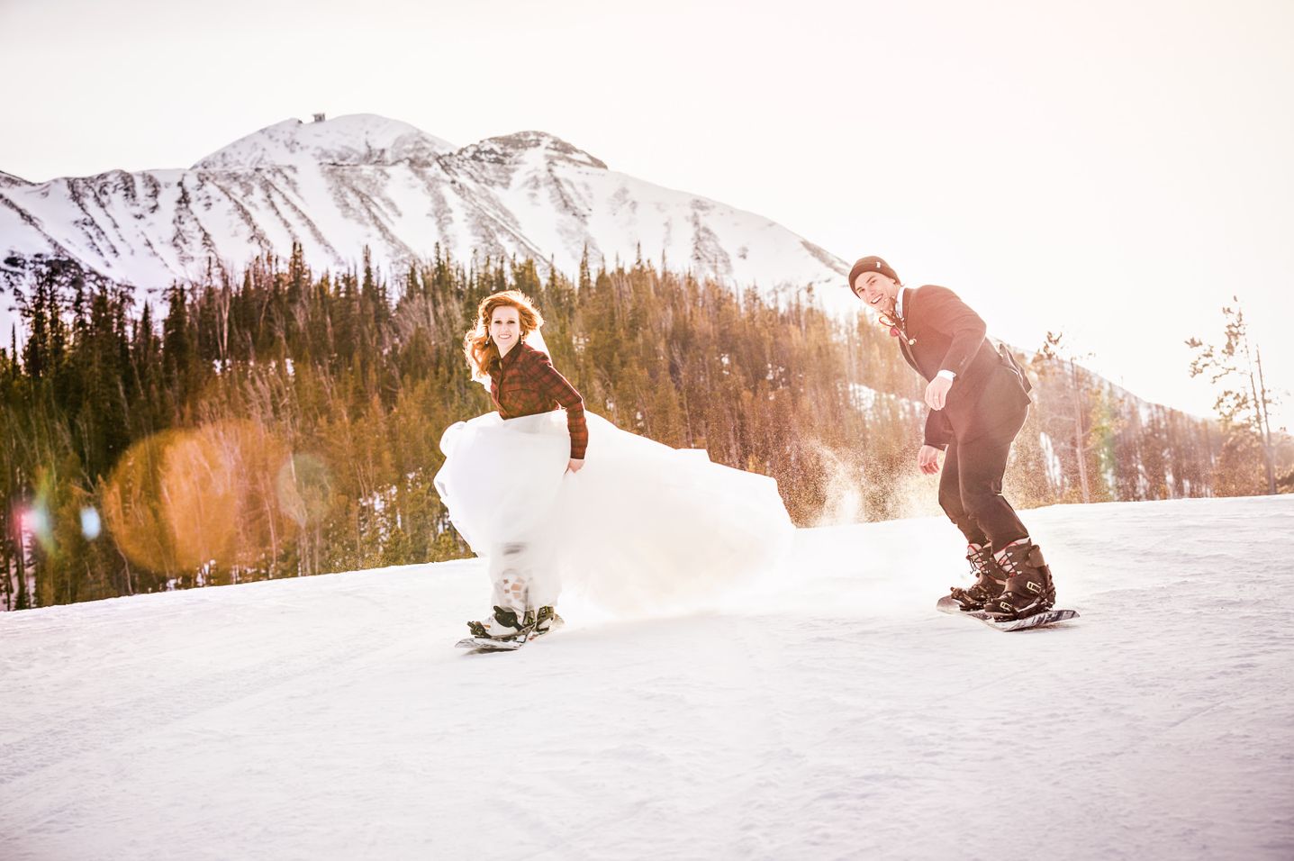 A wedding couple is snowboarding at the Big Sky Resort in Montana.