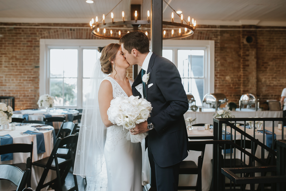 A wedding couple is kissing each other at Station 3 in Houston.