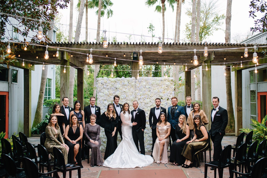 A wedding couple and their guests are standing at the 5226 Elm wedding venue in Houston.