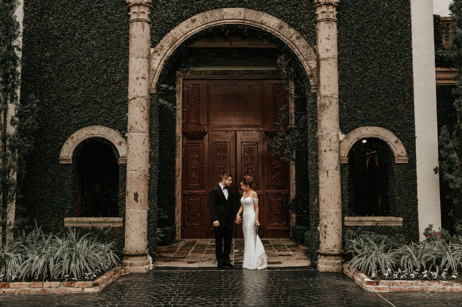 A wedding couple is standing at the Bell Tower at 34th in Houston.