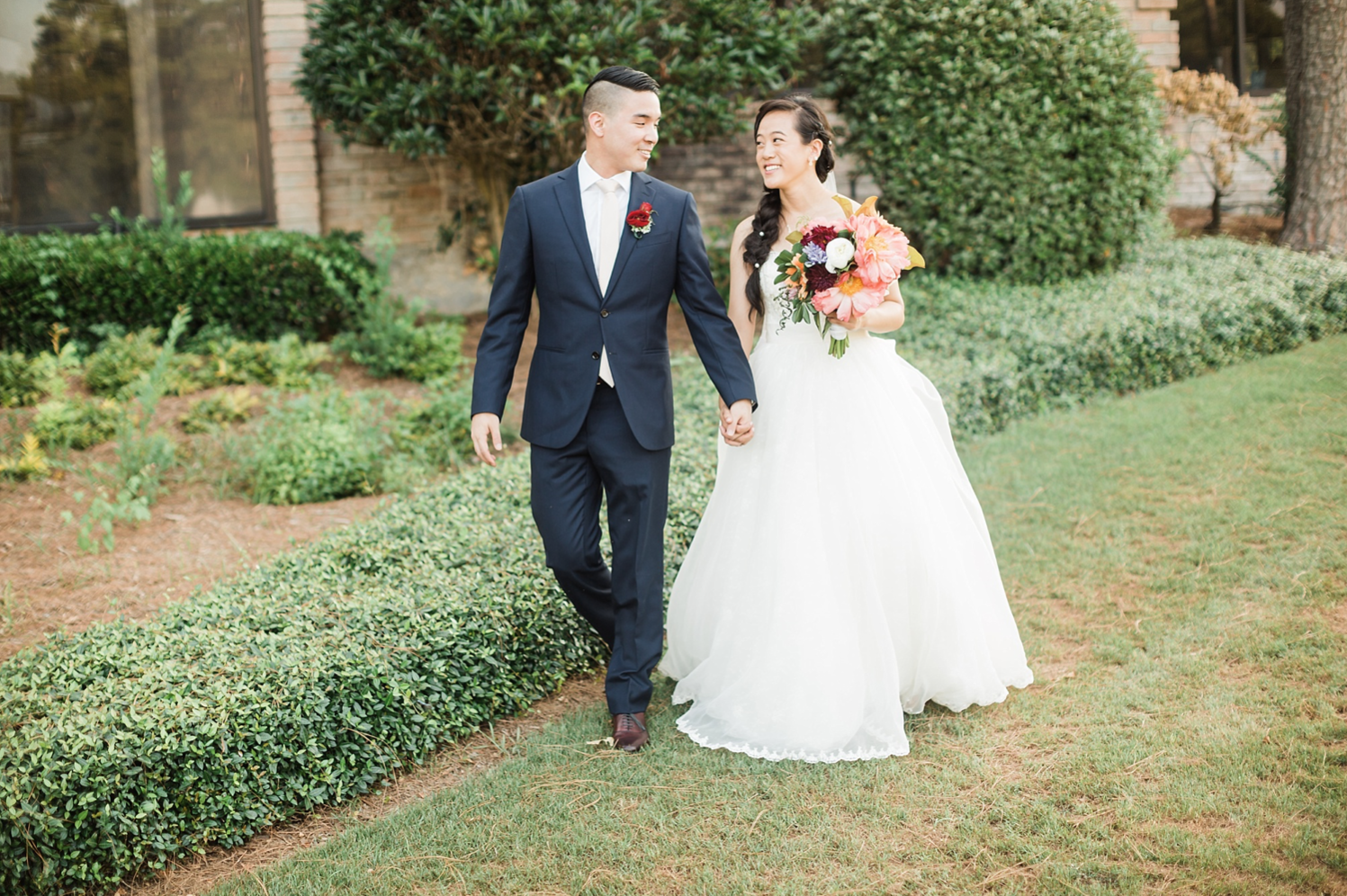 A wedding couple is walking in the garden of the Northgate Country Club.