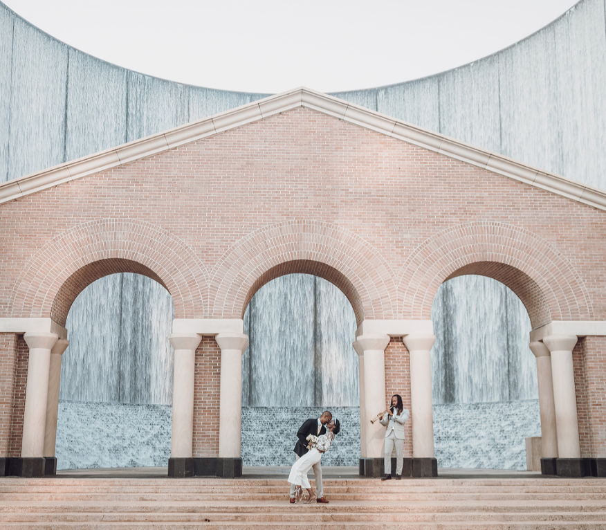 A wedding couple is kissing each other on front of the Gerald D. Hines Waterwall Park.