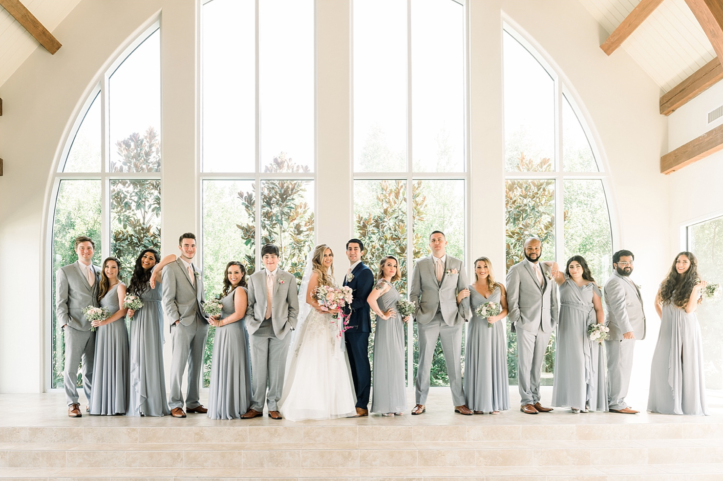 A wedding couple and their bridesmaids and groomsmen are standing in the Ashton Gardens Chapel.