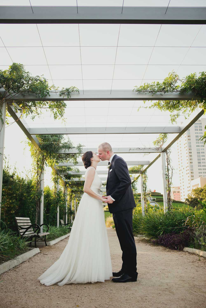 A wedding couple is kissing each other at the The Cherie Flores Garden Pavilion.