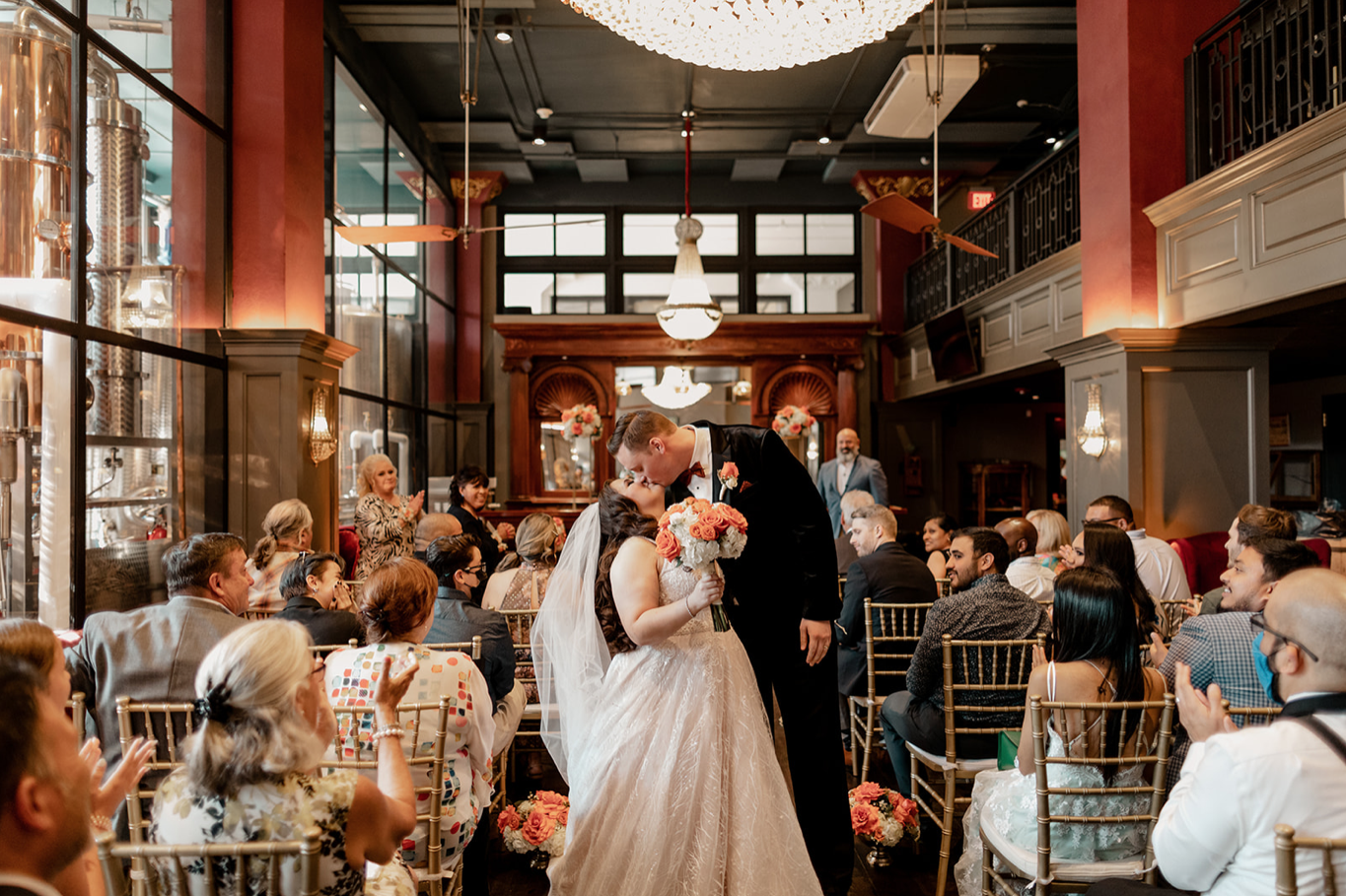A wedding couple is kissing each other and standing next to their guests in the Devils River Distillery.