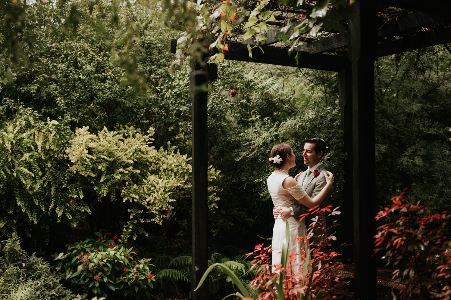 A wedding couple is embracing each other at the San Antonio Botanical Garden .