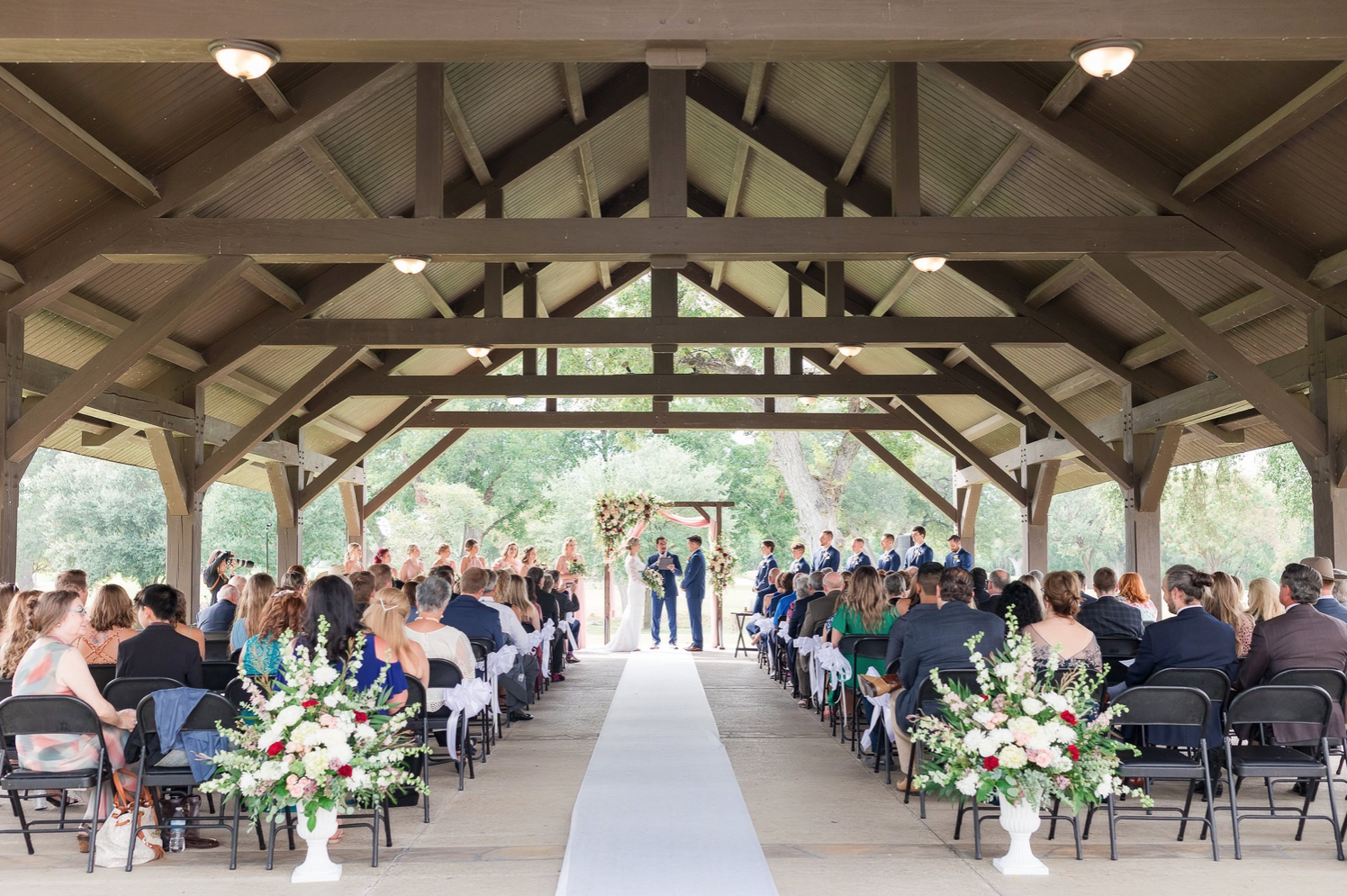 A wedding couple is standing at the altar and their guests are sitting in front of them at the pavilion of the Brackenridge Park Golf Course.
