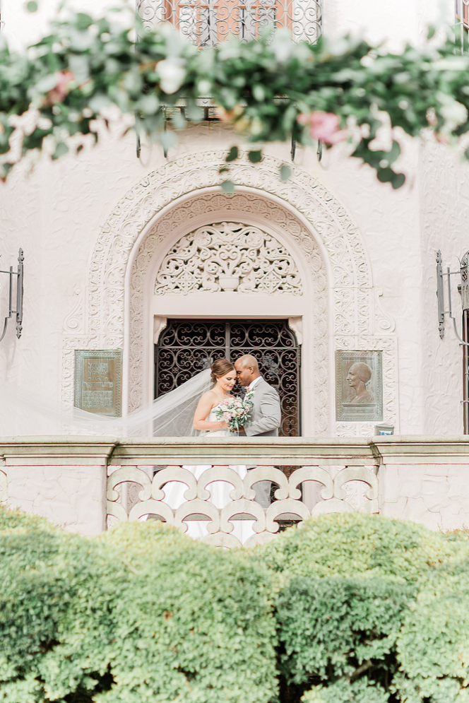 A wedding couple is standing on the balcony of the McNay Art Museum in San Antonio.