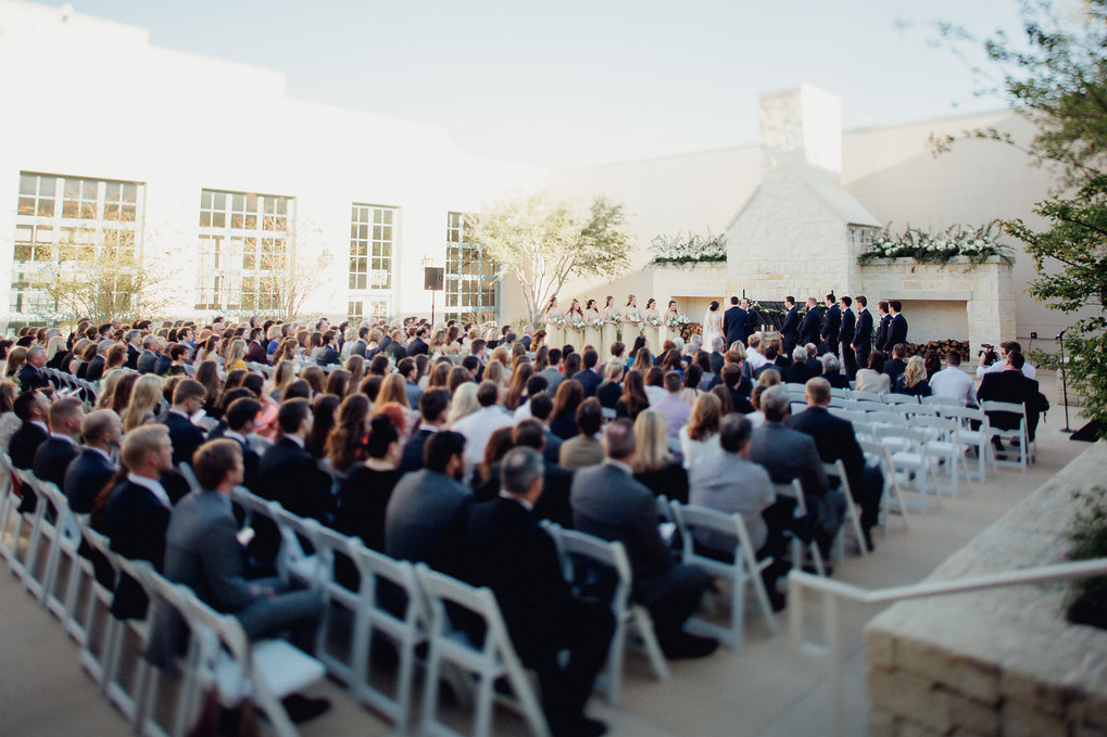 A wedding couple ist getting married at the Hyatt Regency Hill Country Resort and Spa and their guests are sitting in front of them.