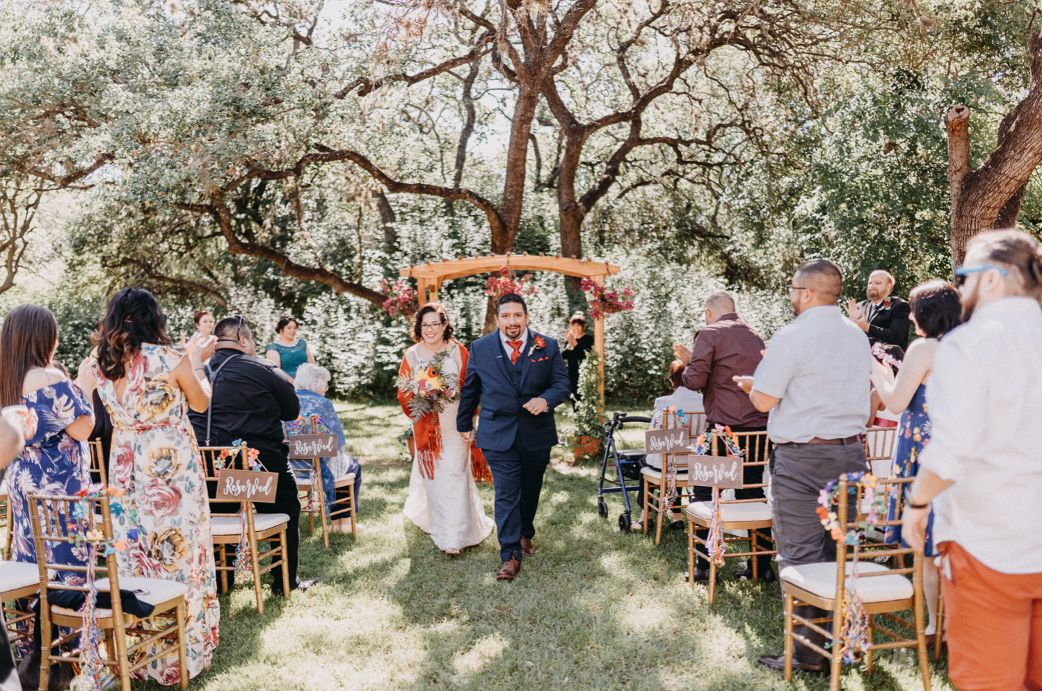 A wedding couple is walking back the aisle with their guests cheering with them.