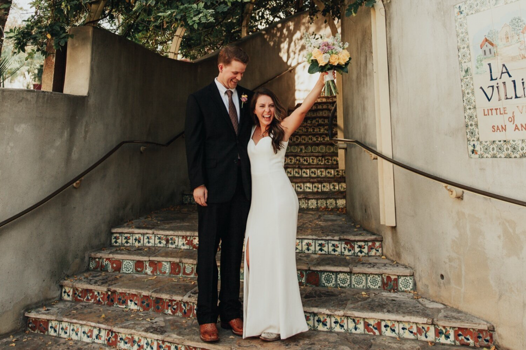 A wedding couple is standing at the stairs of La Villita, one of the wedding venues San Antonio offers.