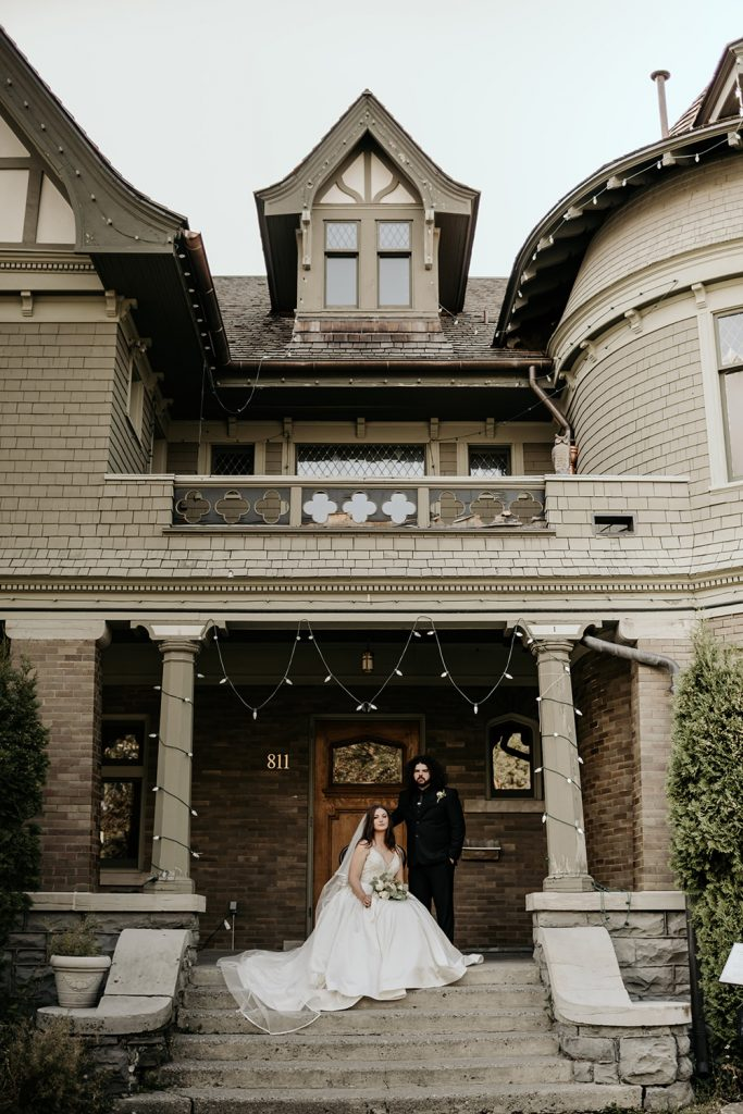 A wedding couple is sitting in front of the Soty Mansion in Montana.