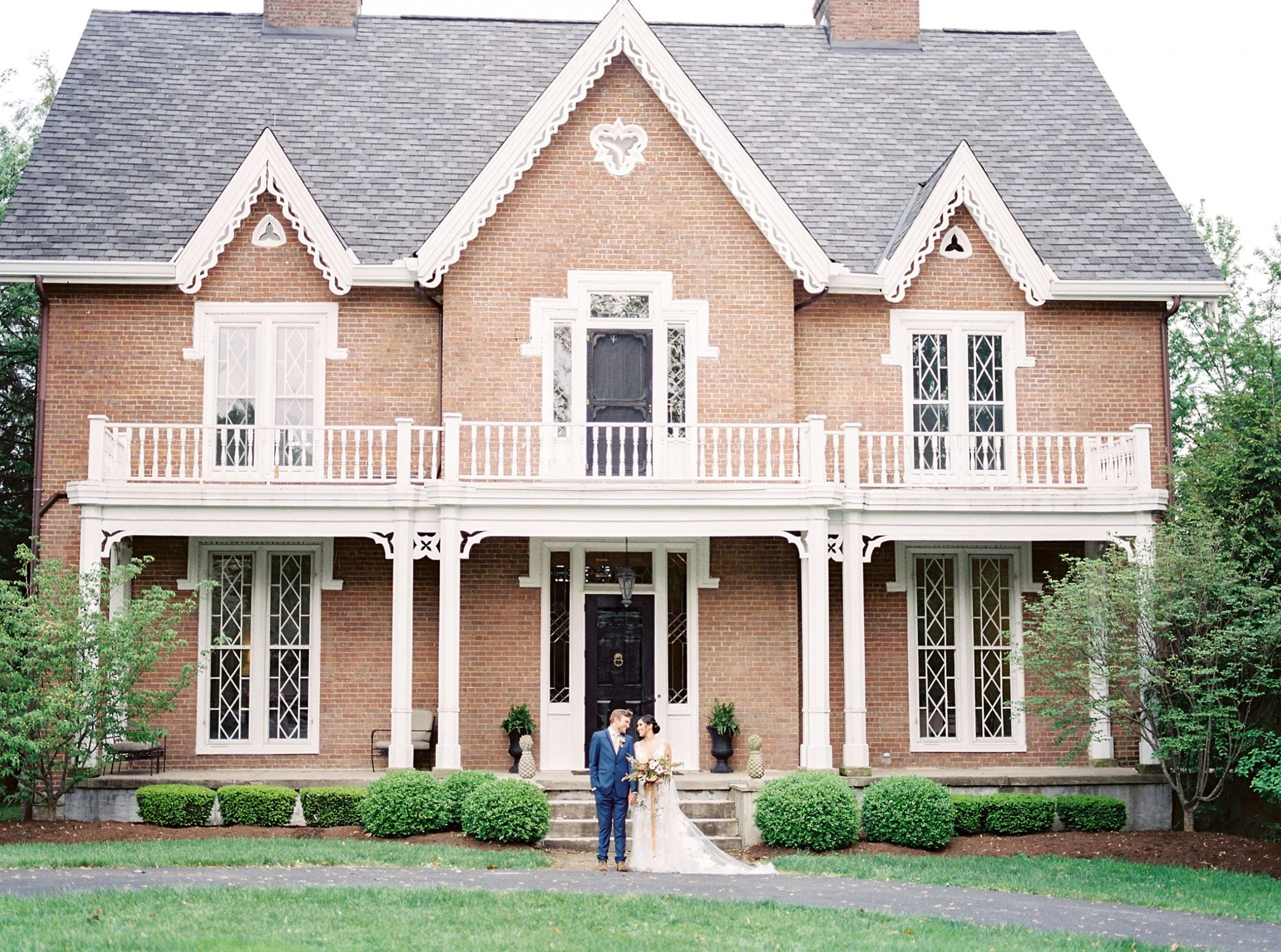 A wedding couple is standing in front of Warrenwood Manor in Kentucky.