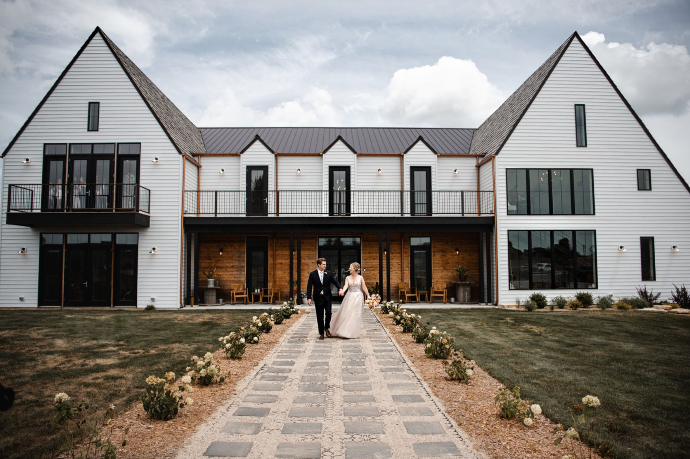A wedding couple is standing in front of the Little Lights on the Lane wedding venue in Iowa.
