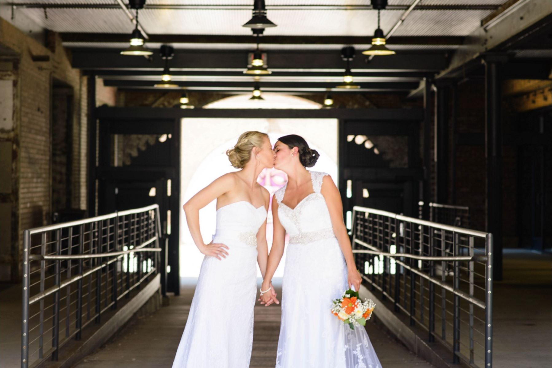 A wedding couple is kissing each other at the Stone Cliff Winery, one of the wedding venues in Iowa.