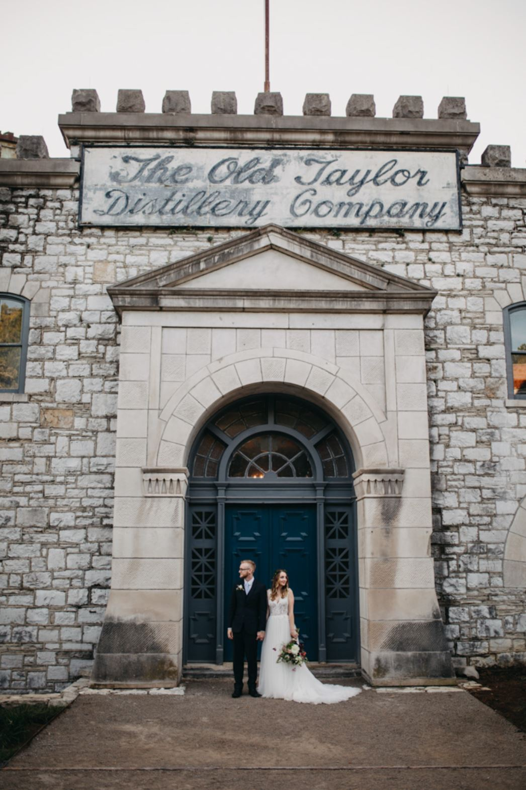 A wedding couple is standing in front of the Castle & Key Distillery in Kentucky.