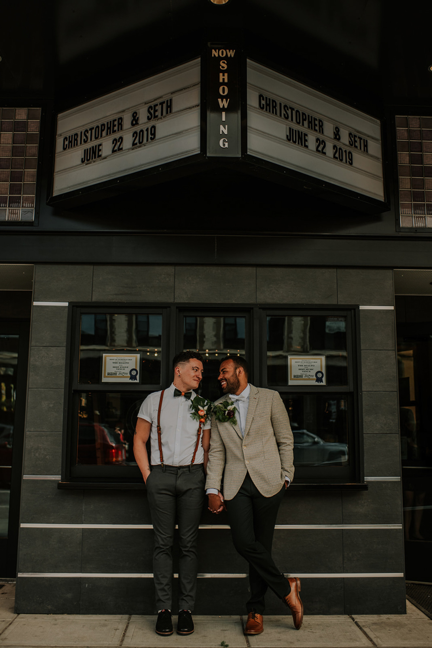 A wedding couple is holding hands and standing in front of the Rialto Bozeman wedding venue.